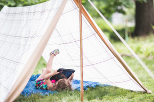 Girl lying on back in homemade garden tent looking at digital tabletの写真素材 [FYI03531206]