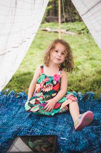 Portrait of girl in homemade garden tent with digital tabletの写真素材 [FYI03531207]