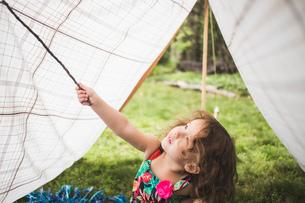 Girl poking homemade garden tent with twigの写真素材 [FYI03531208]