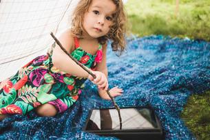 Girl in homemade garden tent using twig on digital tablet screenの写真素材 [FYI03531209]