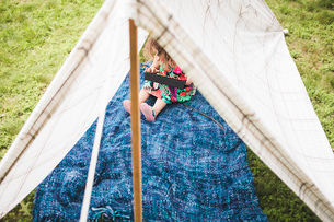 Girl sitting in homemade garden tent using digital tabletの写真素材 [FYI03531211]
