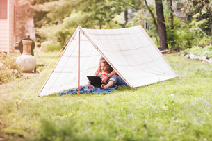 Mature woman and granddaughter sitting in homemade garden tent looking at digital tabletの写真素材 [FYI03531222]