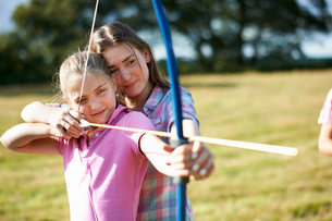 Girl learning archery from teenage sisterの写真素材 [FYI03531432]