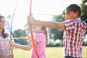 Girl practicing archery with teenage sister and brotherの写真素材 [FYI03531433]