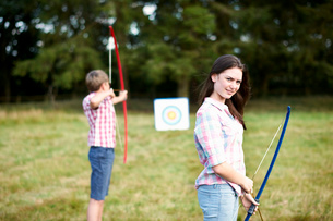 Portrait of teenage girl practicing archery with brotherの写真素材 [FYI03531435]