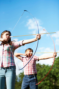 Teenage brother and sister practicing archeryの写真素材 [FYI03531437]