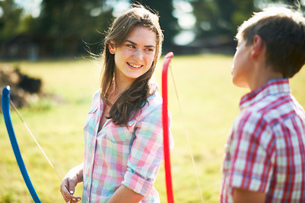 Teenage girl talking to brother whilst practicing archeryの写真素材 [FYI03531439]