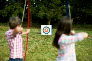 Rear view of teenage brother and sister practicing archeryの写真素材 [FYI03531440]