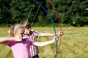 Girl and teenage brother practicing archeryの写真素材 [FYI03531442]
