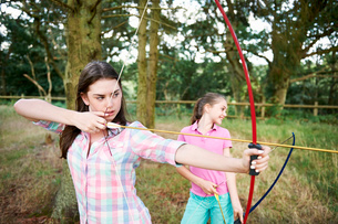 Girl and teenage sister practicing archeryの写真素材 [FYI03531443]