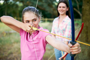 Girl practicing archery aiming with bow and arrowの写真素材 [FYI03531444]