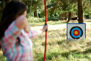 Rear view of teenage girl practicing archery with targetの写真素材 [FYI03531445]