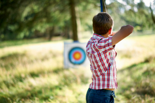 Rear view of teenage boy practicing archery with targetの写真素材 [FYI03531452]