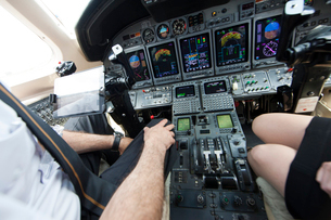 Cropped shot of male and female pilots knees in cockpit of private jetの写真素材 [FYI03531784]