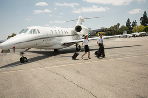 Male and female private jet pilots leaving plane at airportの写真素材 [FYI03531805]