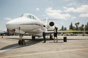 Female businesswoman preparing to  travel in private jet at airportの写真素材 [FYI03531806]