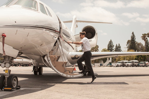 Male private jet pilot boarding plane at airportの写真素材 [FYI03531813]