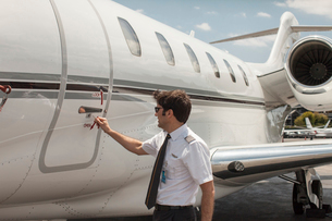 Male private jet pilot locking plane door at airportの写真素材 [FYI03531822]