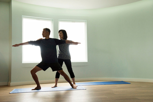 Front view of mature couple doing yoga together, correcting warrior poseの写真素材 [FYI03531898]