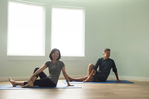 Mature couple sitting on yoga mat leaning on hand, legs crossed looking away smilingの写真素材 [FYI03531900]