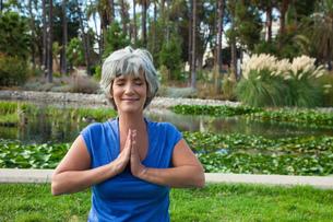 Mature woman meditating in parkの写真素材 [FYI03531940]