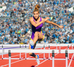 Runner jumping over hurdle on trackの写真素材 [FYI03532035]