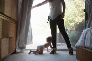 Baby boy holding onto mothers leg in front of patio doorの写真素材 [FYI03532127]