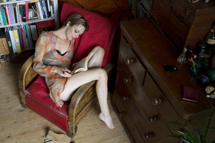 Mid adult woman reclining in retro armchair reading a bookの写真素材 [FYI03532163]