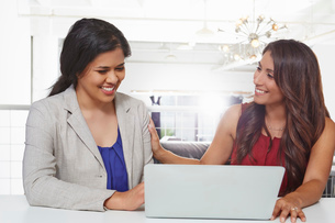 Two businesswomen sitting at desk, looking at laptopの写真素材 [FYI03532195]