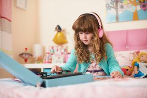 Girl in bedroom wearing headphones and playing vinyl recordsの写真素材 [FYI03532297]