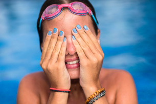 Teenager covering face in swimming poolの写真素材 [FYI03532317]
