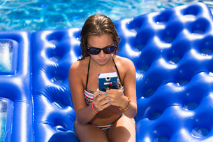 Teenager using smartphone on inflatable in swimming poolの写真素材 [FYI03532318]