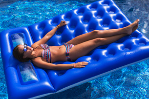 Teenager relaxing on inflatable in swimming poolの写真素材 [FYI03532319]