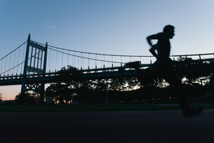 Young man running on race track, sunset, low angle viewの写真素材 [FYI03532366]