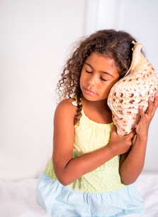 Girl holding seashell to ear, eyes closed listeningの写真素材 [FYI03532456]