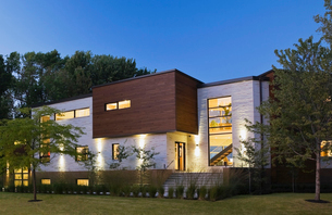 Illuminated beige stone with brown cedar wood modern cubist style residential home facade at dusk, Qの写真素材 [FYI03532518]