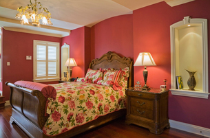 Wooden sleigh bed and night table in master bedroom, cottage style home, Quebec, Canadaの写真素材 [FYI03532556]