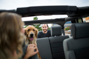 Young woman in jeep looking over her shoulder at dog and boyfriendの写真素材 [FYI03532590]