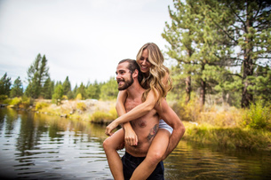 Young man giving girlfriend piggyback in river, Lake Tahoe, Nevada, USAの写真素材 [FYI03532627]