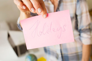 Cropped view of mature womans hands holding handwritten note with the word holidaysの写真素材 [FYI03532770]
