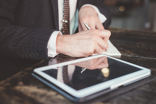 Close up of businessman making diary notes at tableの写真素材 [FYI03532784]