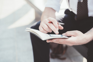 Close up of businessman making diary notes from smartphone on city seatの写真素材 [FYI03532793]