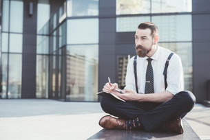 Stylish businessman sitting cross legged making diary notes from smartphone outside officeの写真素材 [FYI03532795]