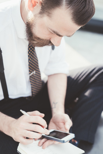 Businessman sitting cross legged making diary notes from smartphone outside officeの写真素材 [FYI03532797]