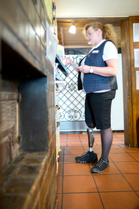 Mid adult woman with prosthetic leg, working cash register at restaurantの写真素材 [FYI03532825]