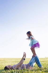 Girl balancing on top of mothers knees in parkの写真素材 [FYI03532939]