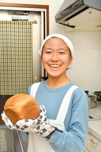 キッチンでパンを焼く女の子の写真素材 [FYI03532942]