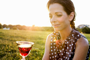 Mature woman contemplating red wine in parkの写真素材 [FYI03532947]
