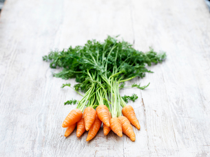 Still life of chantenay carrots with carrot tops on wooden tableの写真素材 [FYI03532956]