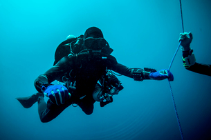 Underwater view of technical diver using a rebreather device to locate shipwreck, Lombok, Indonesiaの写真素材 [FYI03532969]